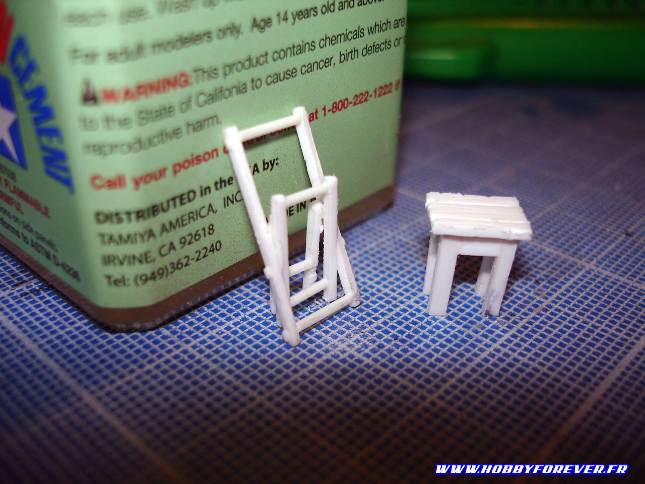 La chaise pliante et la table à côté d'un pot de colle Extra Thin Cement Tamiya